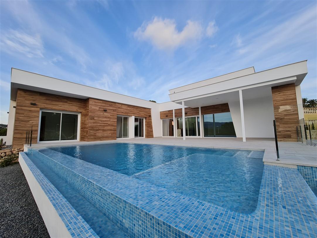 En venta villa de lujo y estilo moderno en Calpe, distribuida en una única planta, con parking privado, piscina y vistas a la montaña.
